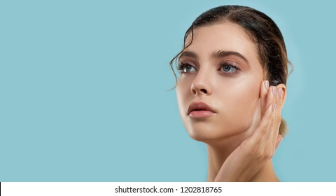 Beautiful young  woman with fresh clean perfect skin cares about her wet moisture skin. Portrait of beauty model with natural make up. Spa, skincare and wellness.
