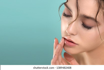 Beautiful young  woman with fresh clean perfect skin. Portrait of beauty model with natural make up and manicure touching lips with balm. Spa, skincare and wellness.
