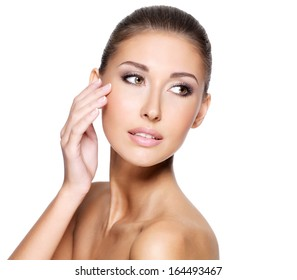 Beautiful young woman with fresh clean skin that touches her face with a hand, isolaten on white