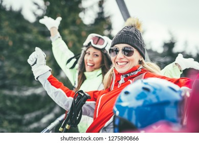 Beautiful young woman friends enjoying in winter vacations. They driving on ski lift and looking at camera with smile.