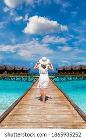 Beautiful young woman in front of water luxury villas standing on the tropical beach jetty (wooden pier) in Maldives island