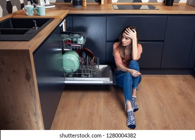 Beautiful young woman frustrated with dishes in a modern kitchen with dishwasher
