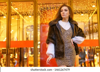 beautiful young woman in fur coat standing next to the store, bright showcase festive mood.