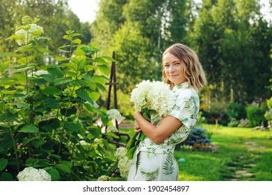 schöner junger Gärtner mit Hydrangea-Blumen im Sommerhüttengarten
