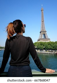 Beautiful young woman gazing at the Eiffel Tower in sunny day