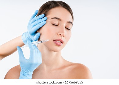 Beautiful young woman gets beauty injection in face isolated over white background.