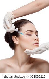 Beautiful young woman gets beauty injection in eye area from sergeant. Isolated over white background.