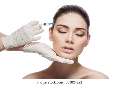 Beautiful young woman gets beauty injection in forehead from sergeant. Isolated over white background.