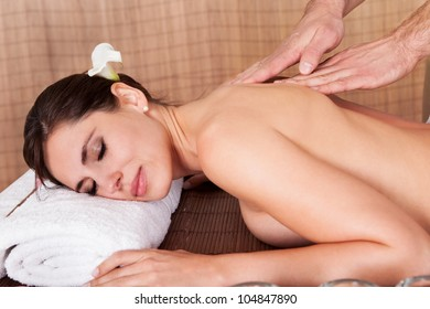 Beautiful young woman getting back massage at spa