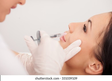 Beautiful young woman is getting botox injection in her face. The expert beautician is holding syringe and filling liquid carefully