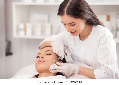 Beautiful young woman is getting botox injection in her cheek. She is lying with closed eyes. The doctor is holding syringe and smiling