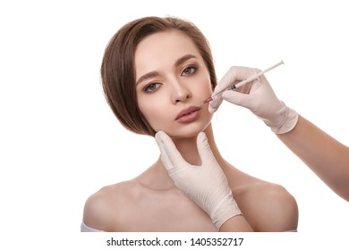 Beautiful young woman getting cosmetic injection in the сheek. Woman in beauty salon. Plastic surgery clinic. Biorevitalization skin therapy. Doctor insert filler. Cosmetology, plastic surgery concept