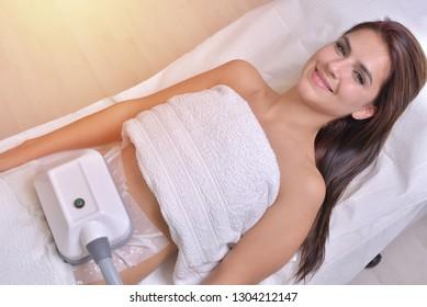 Schöne junge Frau, die eine Kryolipolyse-Behandlung im Kosmetikschrank erhält