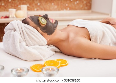 Beautiful young woman is getting facial chocolate mask at spa. She is lying and smiling. The lady has chopped kiwi on her eyes. Aroma candles create relaxing atmosphere