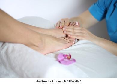 Beautiful young woman getting feet massage
