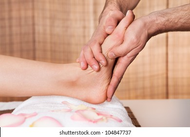 Beautiful young woman getting feet massage treatment at spa