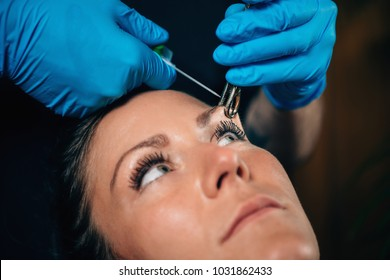 Beautiful young woman getting her eyebrow pierced, body piercer wearing blue gloves