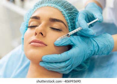 Beautiful young woman is getting an injection in her face, lying with closed eyes