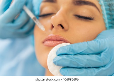 Beautiful young woman is getting an injection in her face, lying with closed eyes, close-up