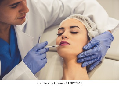 Beautiful young woman is getting an injection in face while lying with closed eyes at the cosmetician