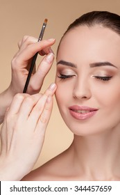 Beautiful young woman is getting make-up at beauty shop. She is sitting and smiling. Her eyes are closed. The visagiste is holding a brush