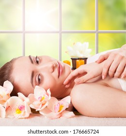 Beautiful Young Woman Getting Massage Facial and Body in Spa Salon. Treatment Cosmetics Beauty Care Body Herbs Surrounded by Flowers