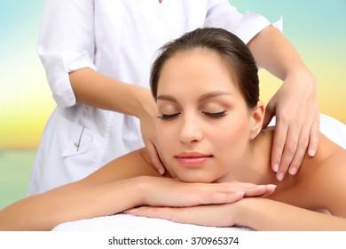 Beautiful young woman getting massage in spa salon