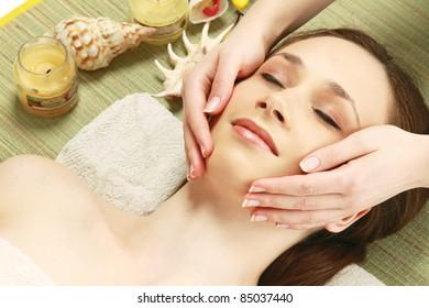 Beautiful young woman getting a massage lying on bamboo mat at spa salon