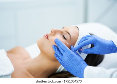 Beautiful young woman getting polydioxanone thread lifting at beauty salon.