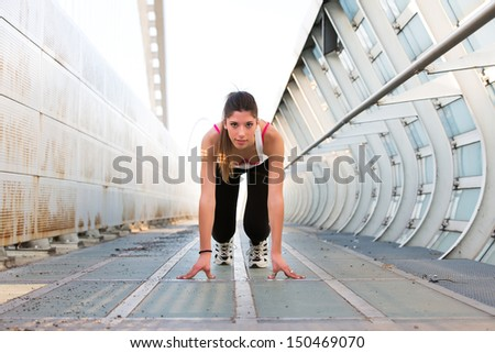 Beautiful young woman getting ready to run on a modern bridge