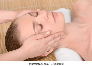Beautiful young woman getting relaxing head  massage in the spa salon. Top view high resolution shot. Model with closed eyes