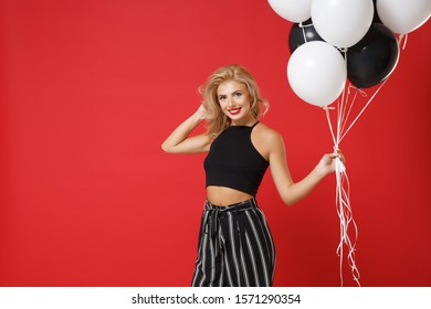 Beautiful young woman girl in black clothes posing isolated on bright red background in studio. Valentine's Day, birthday holiday party concept. Mock up copy space. Celebrating, holding air balloons