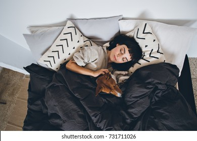 Beautiful young woman or girl cuddles and hugs her best friend basenji puppy dog, sleep together under blankets in hipster designer bed on cold day, peace and quiet