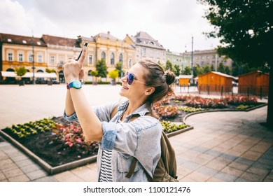 Beautiful young woman girl doing photographing sights on a smartphone while traveling through Europe, Hungary, Debrecen