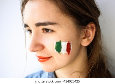 Beautiful young woman girl with painted italian flag on face, football fan supporter