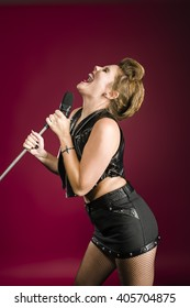 Beautiful young woman glam rock style fashion performing with microphone and singing.