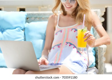 Beautiful young woman with glass of lemonade and laptop at resort