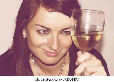 Beautiful young woman with glass of white wine. Nostalgic filter.
