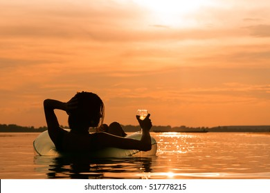 Beautiful young woman with a glass of wine on inflatable ring in water during sunset