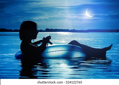 Beautiful young woman with a glass of wine on inflatable ring in water at night