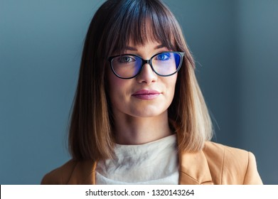 Beautiful young woman with glasses, dressed as casual, on a gray background