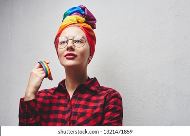 A beautiful young woman with glasses and full lips in a turban and a red shirt holds a rainbow in her hand against a white wall. LGBTQ Lesbians, gays, bisexuals, transgender, queer. Homosexual man