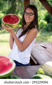 Beautiful young woman with glasses sells fresh watermelon