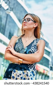 Beautiful young woman in glasses, she stands with arms crossed on the street.