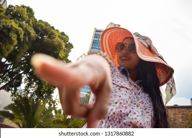Beautiful young woman with glasses and sun hat points at us while smiling in a sensual way in the middle of an urban park