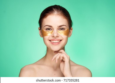 beautiful, young woman with gold patches under the eyes on a green background portrait, spa care, cosmetology