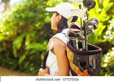 Beautiful young woman as a golf player (focus on equipment)