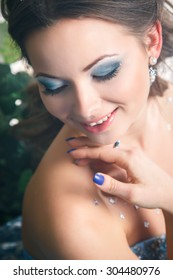 Beautiful young woman in gorgeous blue long dress like Cinderella with perfect make-up and hair style