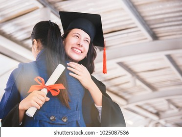 Beautiful young woman graduate hugging her mother at graduate ceremony.