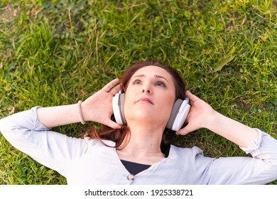 beautiful young woman in gray dress and black cap lying in a park on the grass listening to music with headphones at sunset in spring or summer. concept lifestyle relaxation